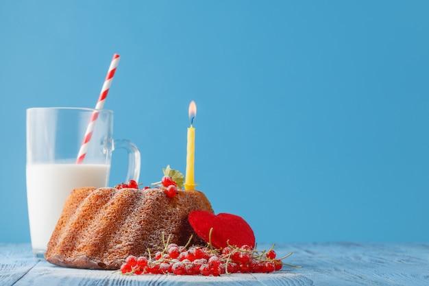 色の背景上のキャンドルで誕生日ケーキ