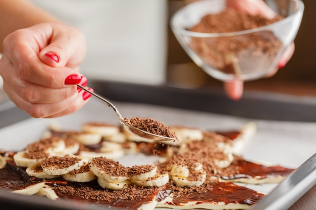 Кондитер покрывает торт растопленным шоколадом