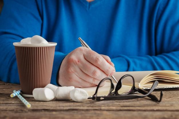 Чашка горячего шоколада и книга с бокалами на деревянный стол