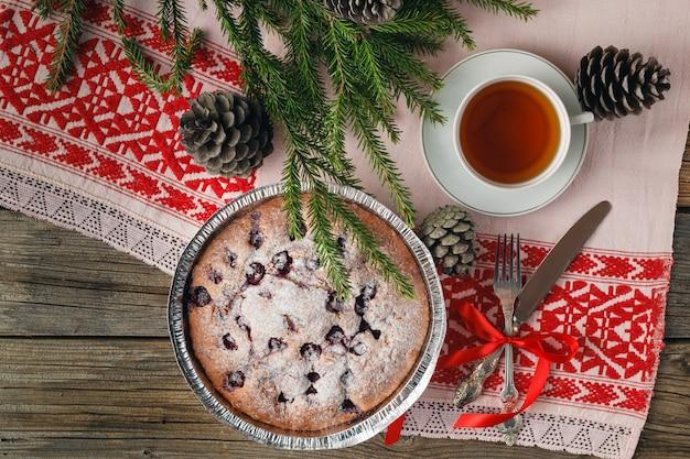 チェリーと木製のテーブルに新鮮な果実と自家製チョコレートケーキ。