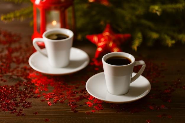 コーヒーと赤いテーブルに銀の星と暗闇の中で輝くクリスマスランタン