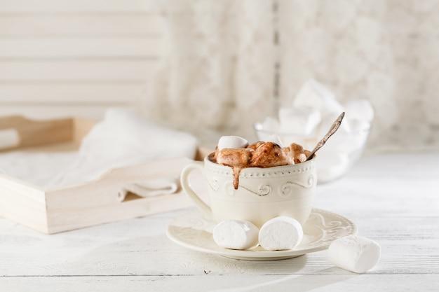 軽い木製のテーブルの上のマシュマロとホットチョコレートのマグカップ