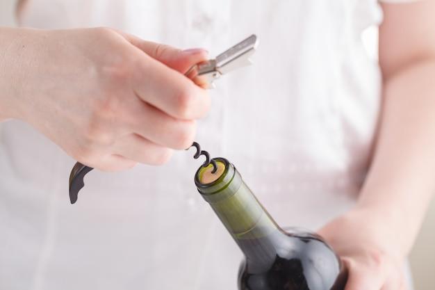 Девушки открывают бутылку вина