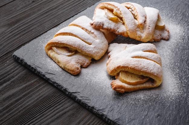 Творожное печенье с яблоком на тарелке с чаем на темном деревянном столе