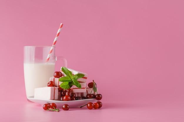 新鮮な牛乳、ピンクのテーブルのチェリードリンク、新鮮なベリーとの各種タンパク質カクテル