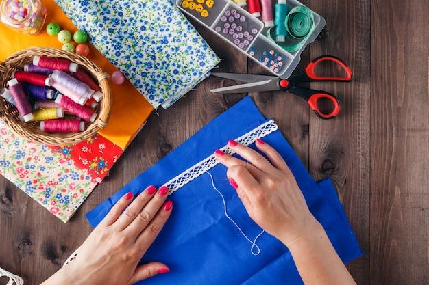 Крупным планом женской руки шить лоскутное шитье