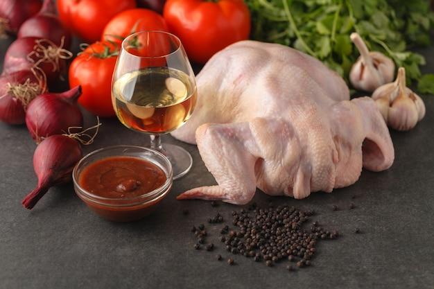 Рецепт приготовления жареной тушеной курицы с зеленью и помидорами. подготовка ингредиентов для приготовления пищи. сырое мясо и свежие овощи
