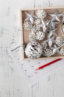 クリスマスのカレンダー。クリスマスプレゼント、木製の白い表面にモミの枝。コピースペース、トップビュー。
