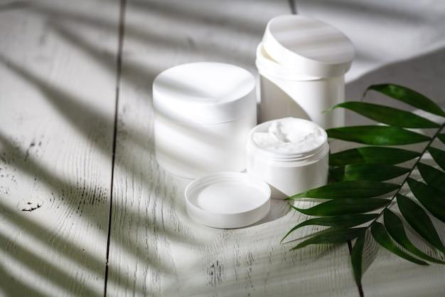 Контейнеры для косметических бутылок с зелеными листьями на белом деревянном столе