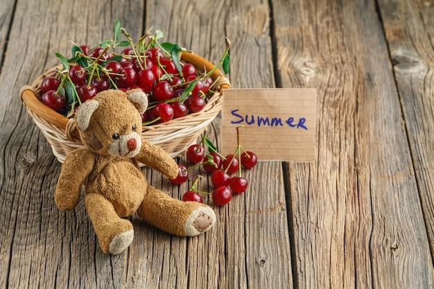 子供のおもちゃとタグの夏のテーブルの上のバスケットにオーガニックチェリー