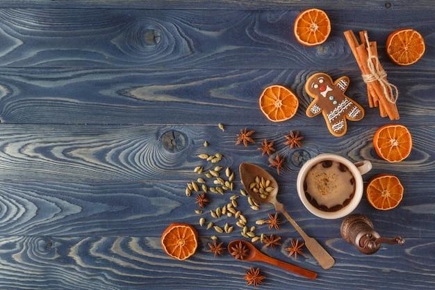 アイシング、お茶、青い木製の背景にモミの木の枝とクリスマスのジンジャーブレッドクッキー。クリスマスのグリーティングカードのコレクションです。コピースペース。上面図