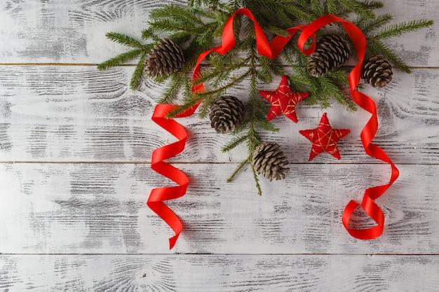 雪とスプルースの枝の赤いクリスマスの装飾