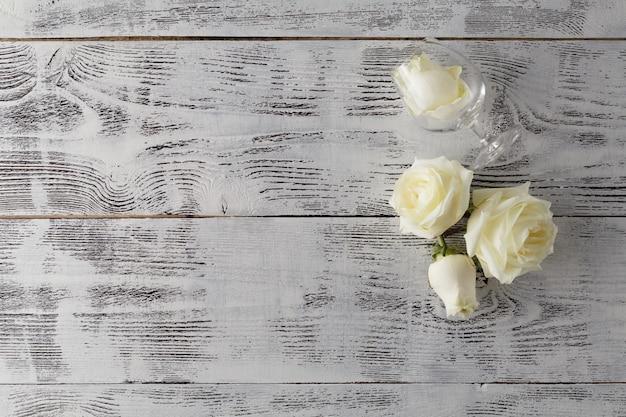 バレンタイン背景、白いバラの花と花びらが白い素朴な木、コピースペース平面図に散在しています。幸せな恋人たちの日のモックアップ