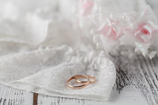 Обручальные кольца на белом атласе