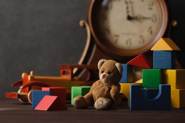 Игрушка медведь и деревянные блоки на столе