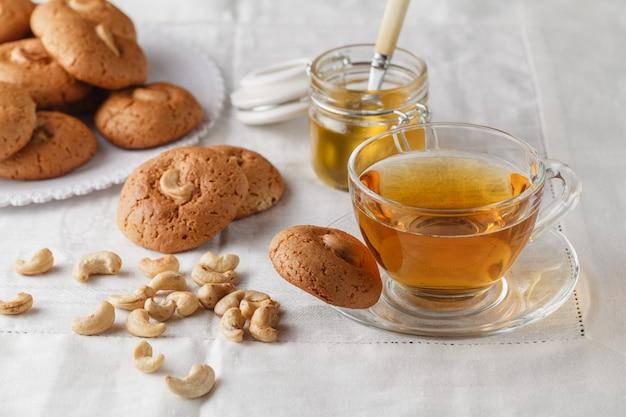Чашка горячего чая и овсяное печенье с орехами