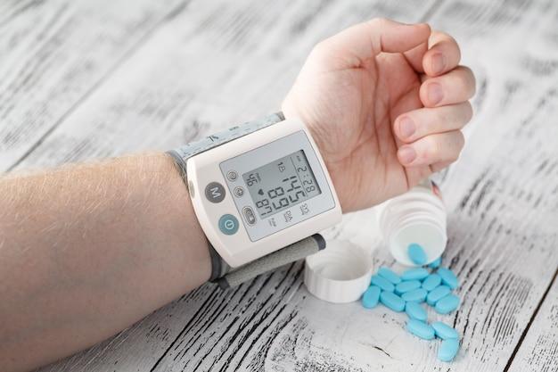 Тонометр с высоким показателем артериального давления на руке мужчины. таблетки гипертонии медицинские