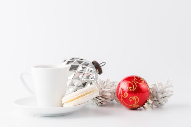 Новогоднее украшение и маленькая чашка кофе на белом