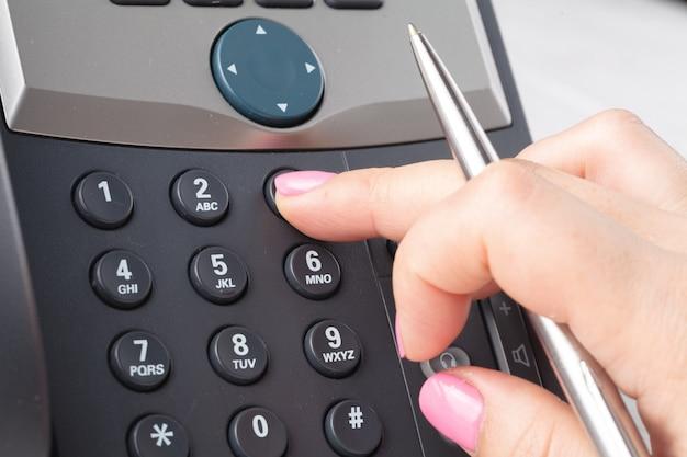 コールセンターやオフィスの電話のコンセプト、電話パッドの女性の指プレス番号