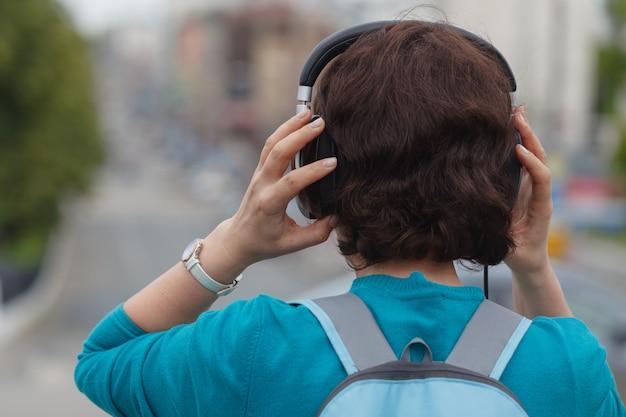 市内のヘッドフォンで音楽を聴く美しいブルネットの女性