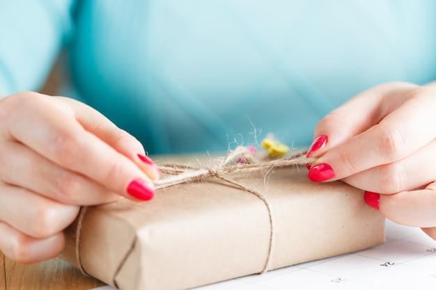 女性は贈り物に古典的な弓をバインドします