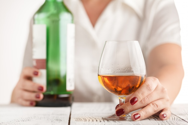 白い表面にアルコールを飲む女性