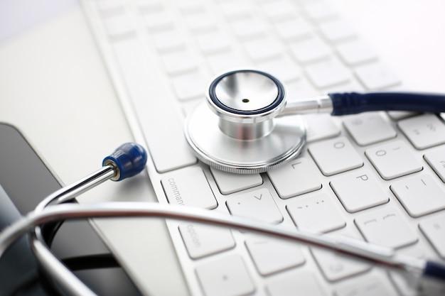 医者のオフィスの作業台で銀のキーボードの上に横たわる医療聴診器ヘッド
