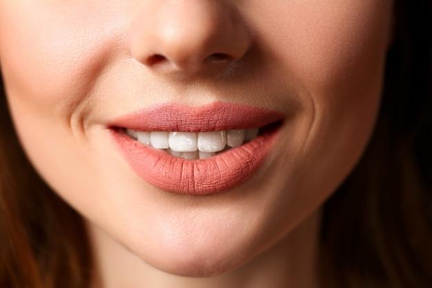 Улыбающаяся женщина закрыла красные губы крупным планом