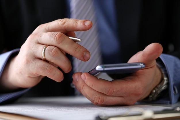 スーツの男性の腕は、職場のクローズアップで携帯電話と銀のペンを保持します。