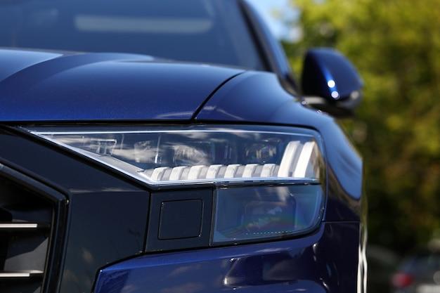 Фары и бампер дорогого современного автомобиля на открытой городской парковке