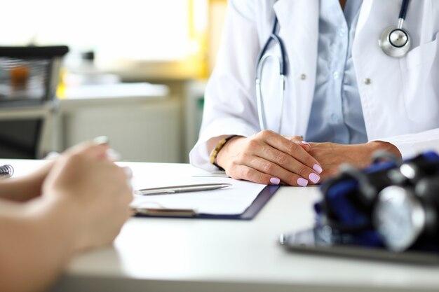 Терапевт в клинике принимает больного посетителя, обсуждая жалобы на здоровье