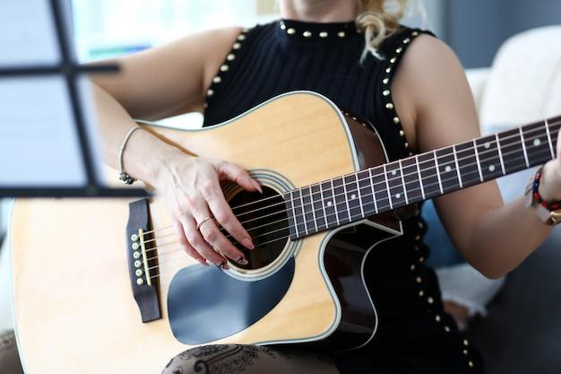 Женские руки держат западную акустическую гитару, сидя на диване у себя дома