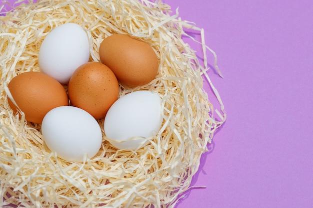 Закройте коричневые и белые яйца в гнезде соломы