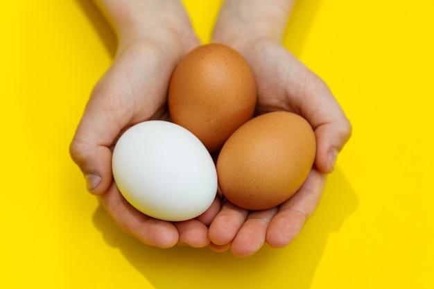 Руки ребенка, держа куриные яйца