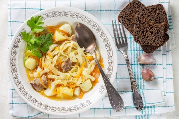 スプーンとフォークを使った綿ナプキンにセロリと野菜と麺と自家製チキンスープ。ナプキンにライ麦パンの部分。