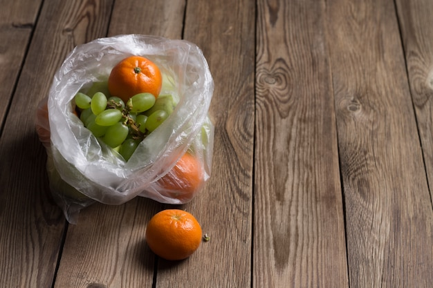 自然な木製テーブルの上のビニール袋に果物(みかん、リンゴ、ブドウ)。この画像は、ビニール袋が食品に及ぼす悪影響を示しています。