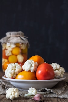 発酵野菜の準備。新鮮なトマト、手前のプレートのカリフラワー。素朴なスタイル
