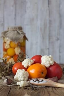 Приготовление сброженных овощей. свежие помидоры, цветная капуста, специи на переднем плане.
