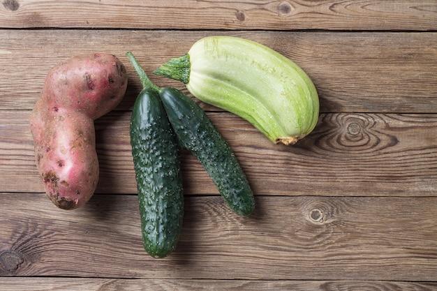 Модный уродливый органический натуральный картофель, огурец и тыкву на натуральный деревянный стол. копировать пространство