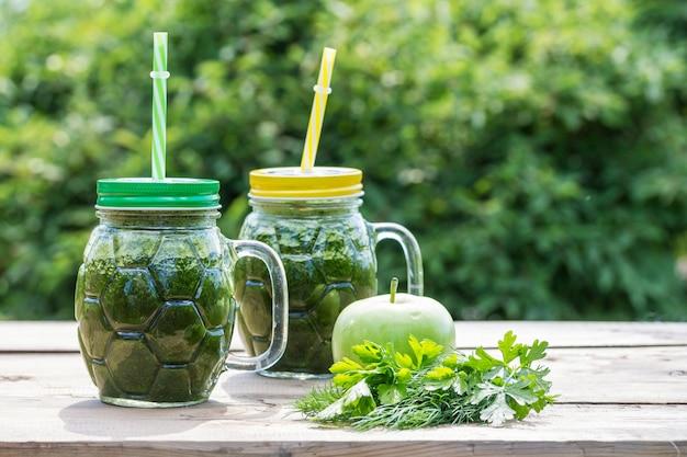 健康的な緑のスムージーと成分-パセリ、ディル、ストローでガラスの瓶にリンゴ。スーパーフード。コピースペース。