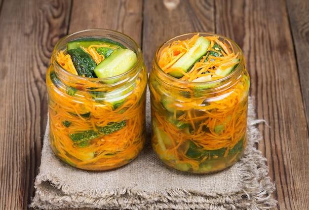 Традиционная корейская закуска из огурцов кимчи в двух стеклянных банках: огурцы, маринованные с морковью, острым перцем и чесноком, с растительным маслом, на салфетке.
