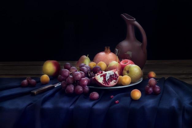 暗い青のリネンテーブルクロスのプレート(ザクロ、赤ブドウ、リンゴ、ナシ、アプリコット)のワインとフルーツの水差しのある静物。水平方向。