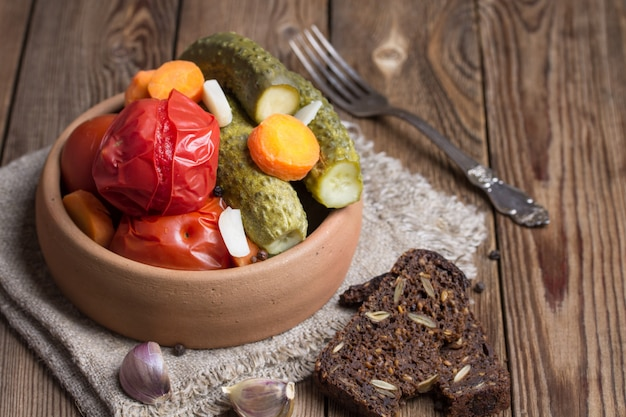 Маринованные помидоры и огурцы в глиняной посуде, с ржаным хлебом на деревянном столе.