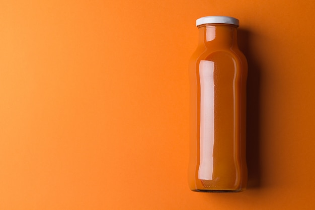 Морковный сок в стеклянной бутылке на оранжевом фоне градиента бумаги. минимализм
