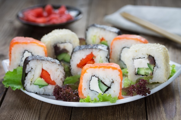 Суши роллы на белой тарелке с имбирем и кухонной салфеткой.