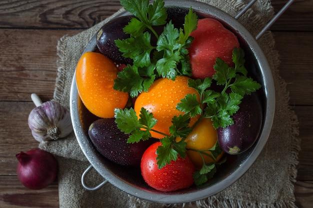 パセリトマト、木製のテーブルのザルでナスの新鮮な野菜