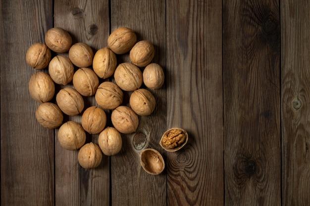 Грецкие орехи в форме сердца на деревянном столе. копировать пространство.