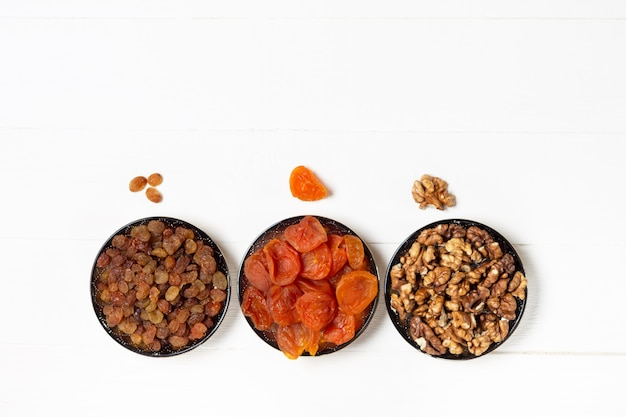 Сушеный абрикос, изюм, грецкий орех в блюдцах, стоя в ряд