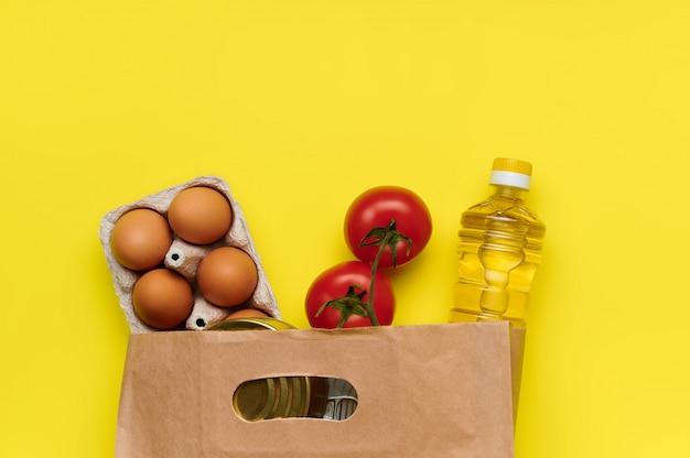 Яйца, помидоры, консервы, масло в бумажном пакете на желтом