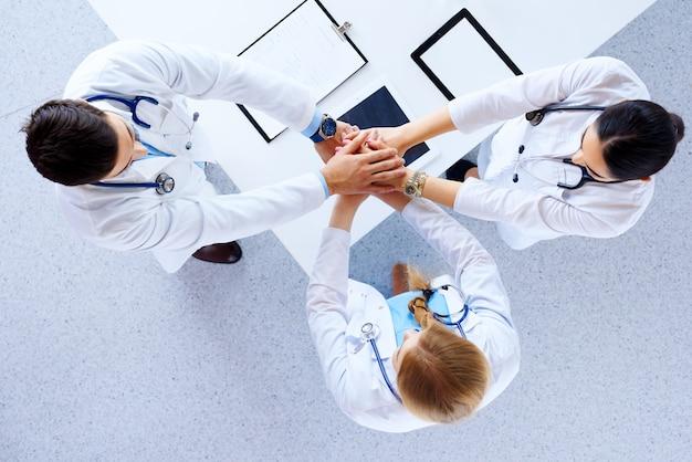 Профессиональные врачи рукопожатие в больнице. плоская планировка, вид сверху